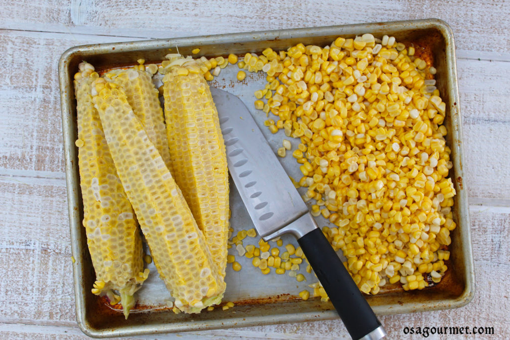 Corn Kernels Cut From The Cob on a tray with a knife