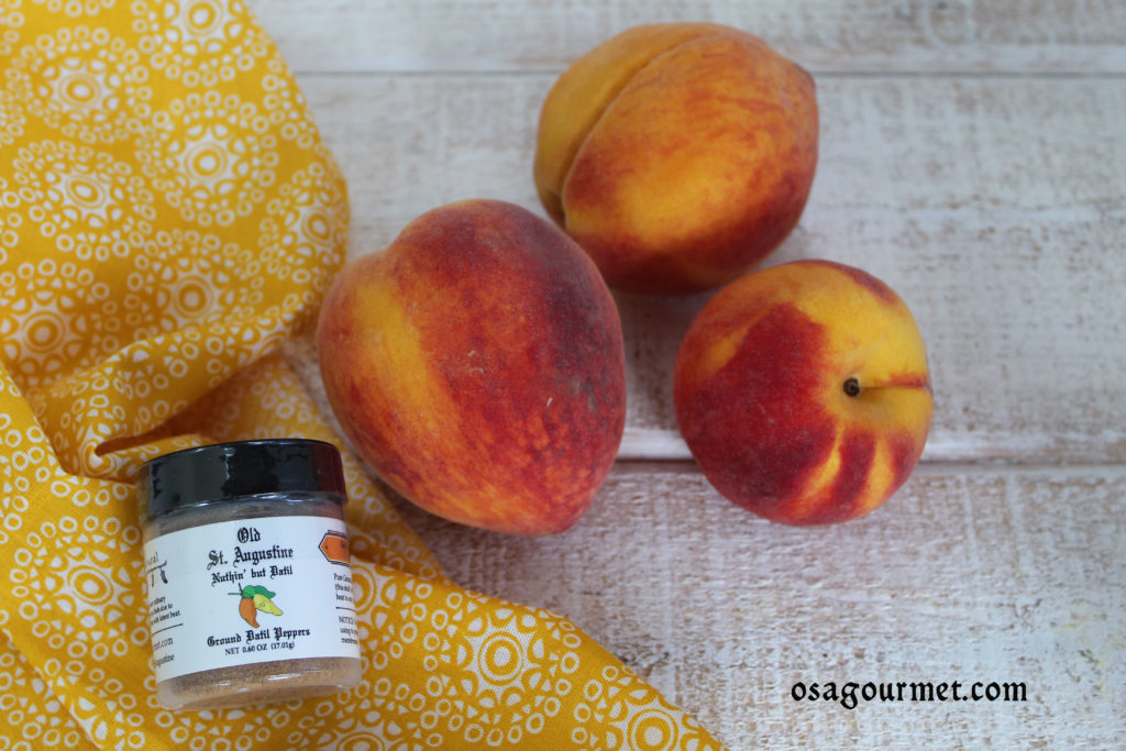 3 ripe peaches on a yellow napkin with OSA Gourmet Nuthin' But Datil pure ground datil pepper