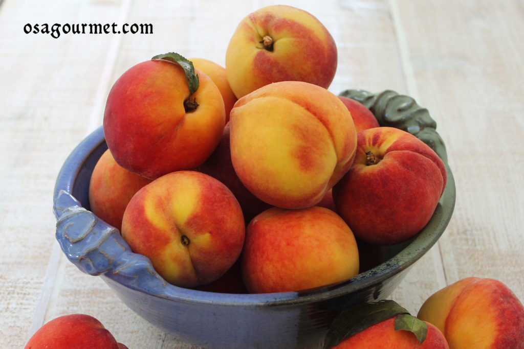 ripe juicy peaches in a blue and green bowl