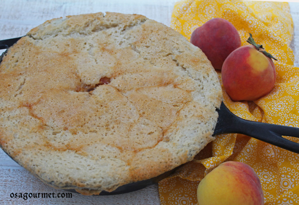 Peach cobbler in a skillet with fresh peaches on a yellow napkin