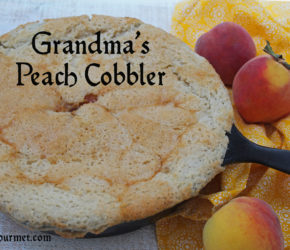 Grandma's Peach Cobblerr in a skillet with fresh peaches