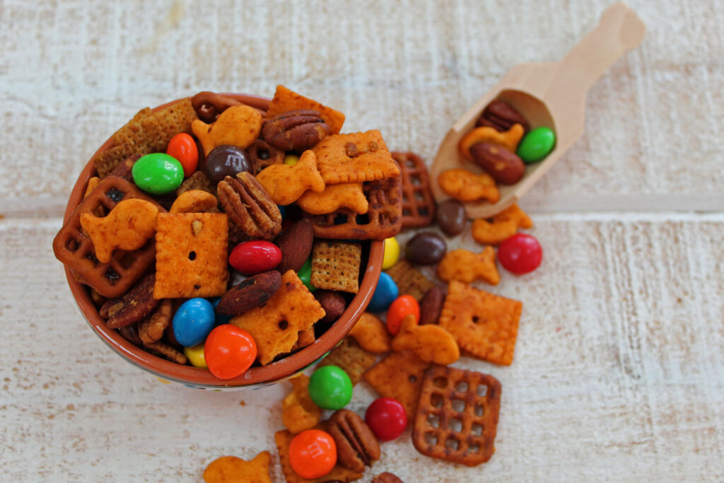trail mix in a little bowl with a wooden scoop