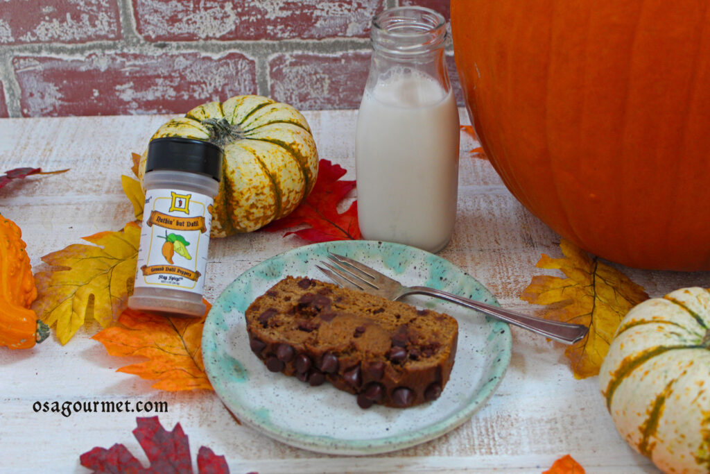 slie of pumpkin chocolate chip bread on a plate with bottle of Nuthin' but Datil and glass of milk
